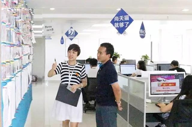2 圖為工作人員帶著企業嘉賓參觀名淘教育廣西分公司,講解公司背景文化墻內容.webp.jpg
